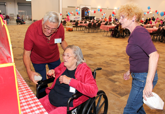 Volunteer Nick Vallejo assists with carnival games during the eighth annual County Fair hosted by Precinct 4's Senior Adult Program.